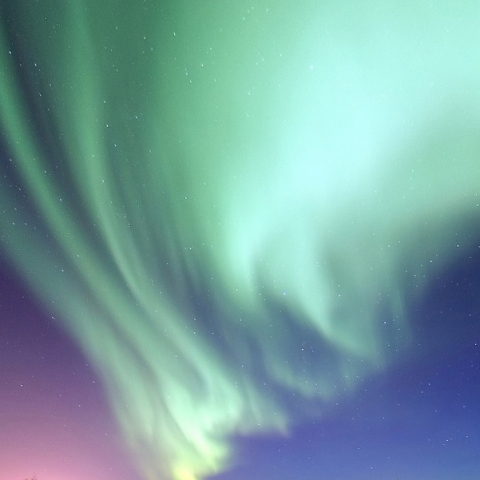 Pink, purple, blue and green lights created by gas particles colliding in the sky