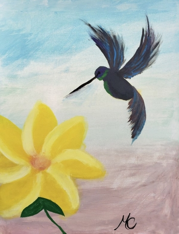 Hummingbird hovering over big yellow flower