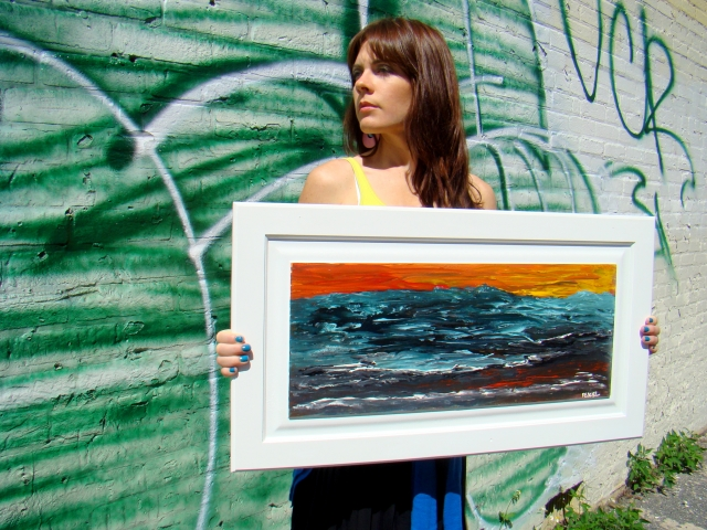 Artist Rachael Harbert holds abstract landscape painting of a sea in tumult as the sun sets entitled Angry Sea
