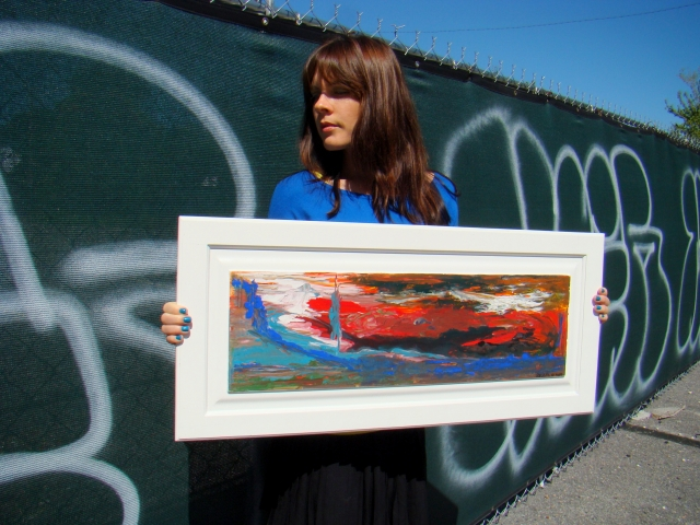 Artist Rachael Harbert holds abstract landscape painting of a red and blue sky entitled Sky on Fire in front of graffiti wall