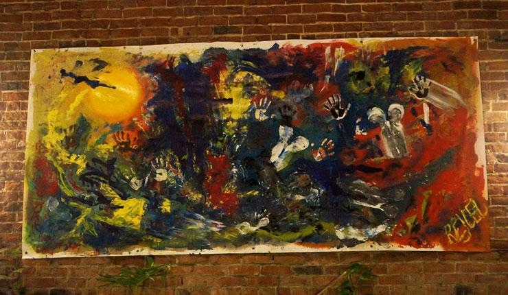A large, colorful abstract painting by Rachael Harbert hangs on a brick gallery wall