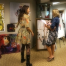 Artist Rachael Harbert paints to one of her paintings as she speaks with a person attending her art show