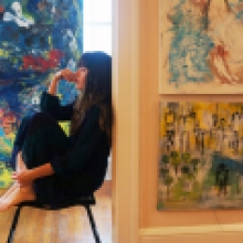 Rachael sits in her home studio with her paintings around her