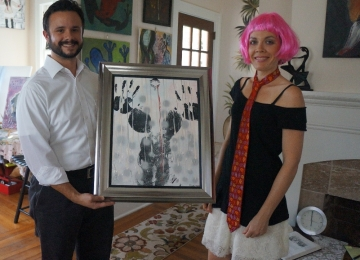 Artist Rachael Harbert hands over one of her paintings to a client