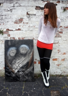 Artist Rachael Harbert stands next to black and white abstract painting Ralphie as it leans against a white corroding brick wall