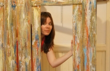 Rachael stands within a large mixed media art installation