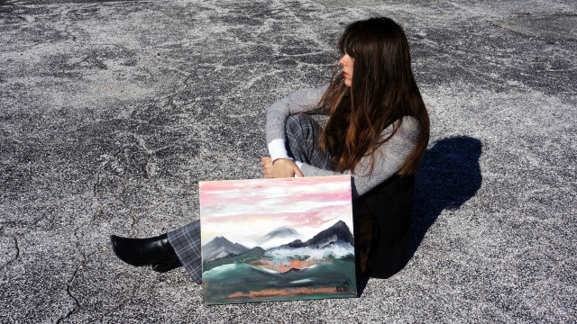 Artist Rachael Harbert sits next to abstract painting of fog falling into the valley of a mountain range entitled Mountains in Fog