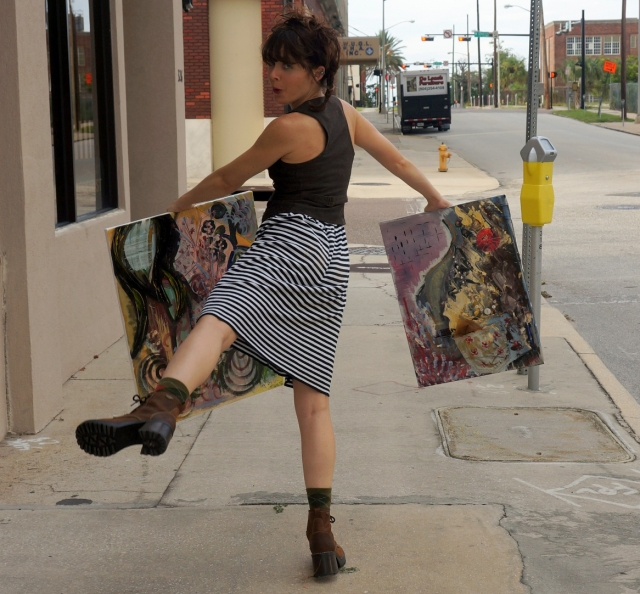 Artist Rachael Harbert dancing along a sidewalk holding two abstract paintings