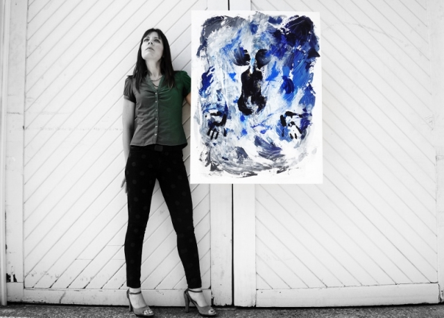 Artist Rachael Harbert holds blue abstract art painting of a naked woman under water