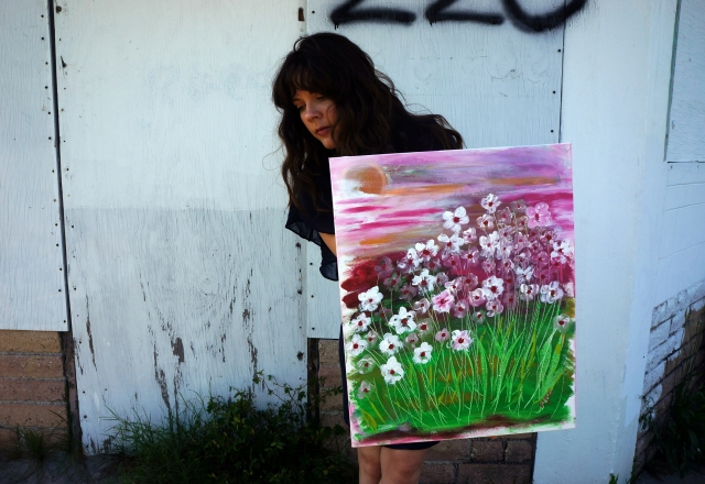 Artist Rachael Harbert holds her painting entitled Wild Periwinkles in front of a building with the numbers 220 spray painted on it