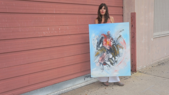 "Artist Rachael Harbert holds abstract painting ""Inception"" in front of large mauve metal door"