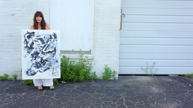 "Artist Rachael Harbert holds abstract painting ""Jumping Beans"" in front of white wall and door"