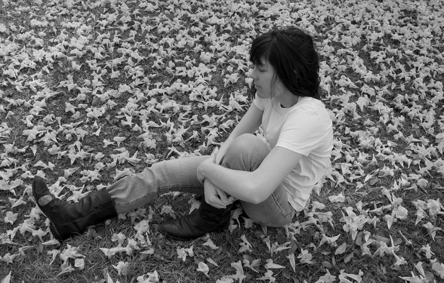 Black and white photo of artist Rachael Harbert sitting on the ground that is covered in flower petals