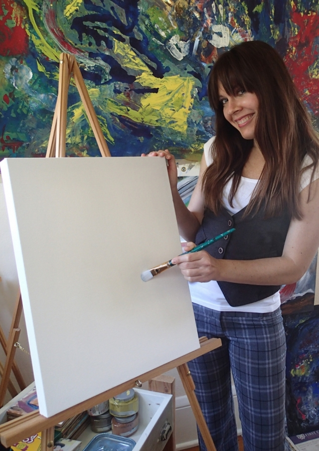 Abstract artist Rachael Harbert stands next to a blank canvas on a easel with a paint brush in her hand