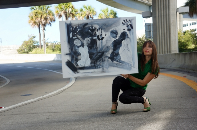 Rachael holds her abstract painting entitled Black and White as she crouches on a highway's exit ramp