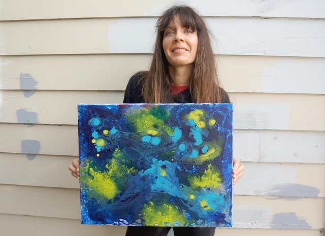 Artist Rachael Harbert holds an abstract elemental painting entitled Cerulean Blue
