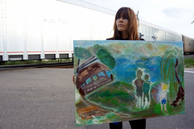 Artist Rachael Harbert holds painting Smith Mountain Lake as an Amtrak train goes by