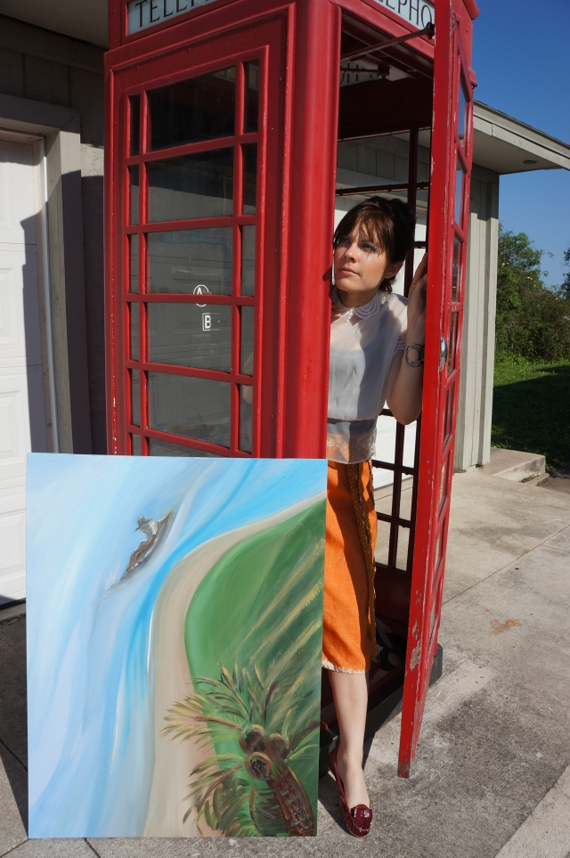 Artist Rachael Harbert peeks out from behind a red telephone booth while her painting entitled Balcony View leans against the booth