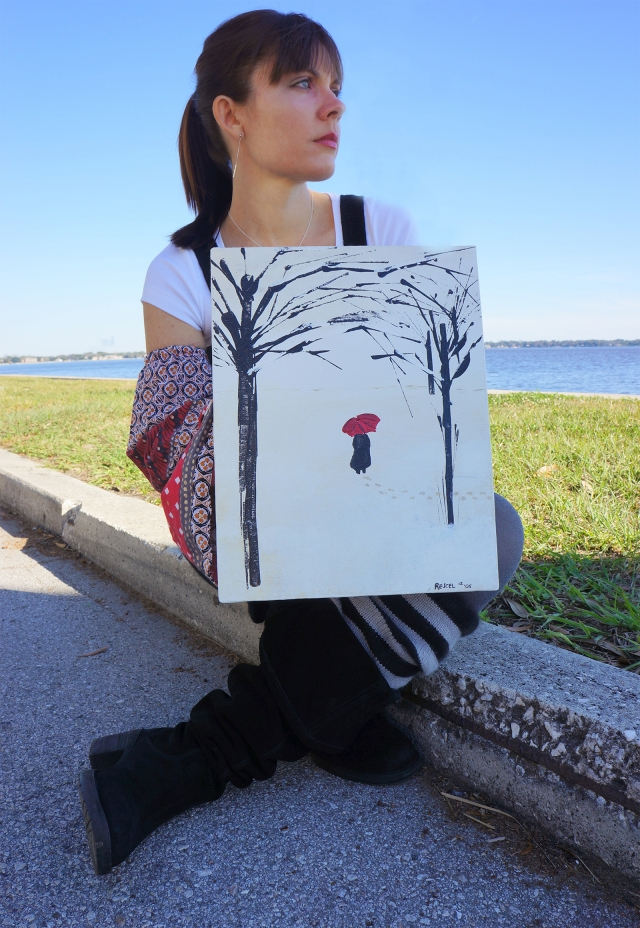 Rachael sits on curb holding painting A Lonely Walk