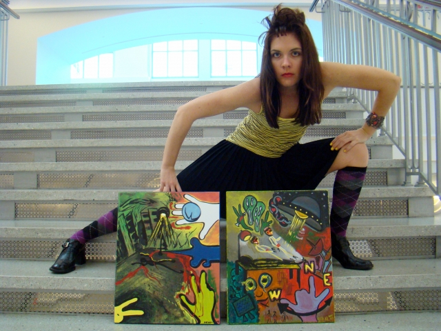 Artist Rachael Harbert poses next to paintings Shadowplay and Extraterrestrial on the stairs of a large library
