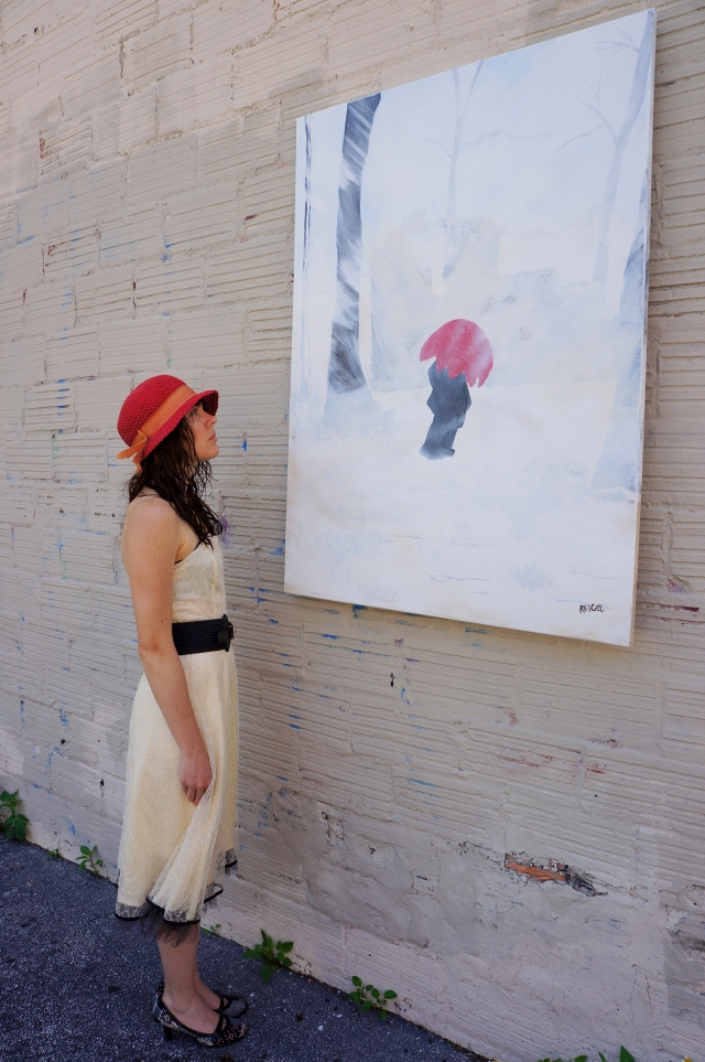 """Artist Rachael Harbert stands looking at painting """"White Storm"""" as it hangs on a painted cement block wall"""