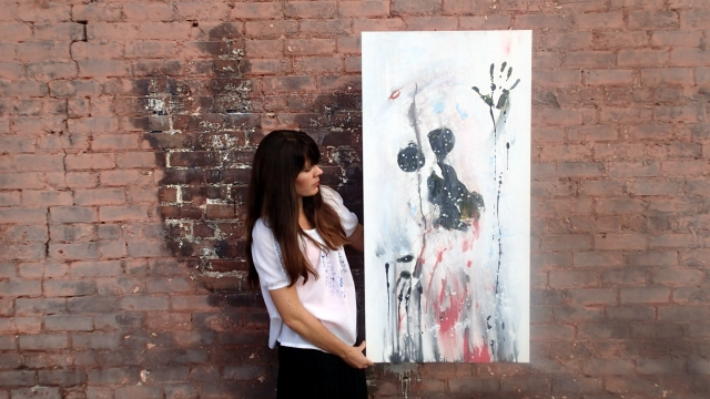 Artist Rachael Harbert holds painting Still Shot in front of a dirty pink brick wall