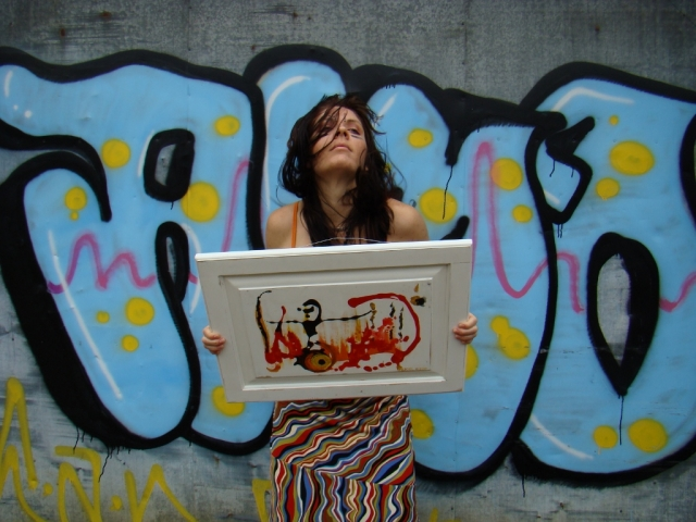 Rachael stands in front of wall with huge blue graffiti letters holding painting Pyromaniac