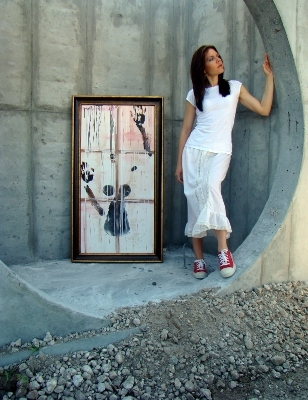 Artist Rachael Harbert standing in concrete structure of urban core with a painting leaning on the structure