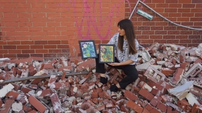 Artist Rachael Harbert sitting in urban core rubble holding two paintings