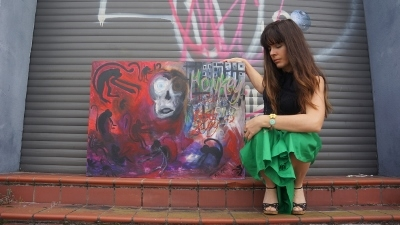 Artist Rachael Harbert squatting next to painting on steps of building with graffiti within the urban core
