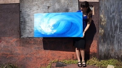 Artist Rachael Harbert holding painting in front of house within the urban core