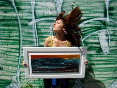Artist Rachael Harbert holding painting on side of building with a graffiti wall within the urban core