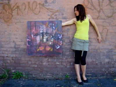 Artist Rachael Harbert standing in front of brick and graffiti building within the urban core holding a painting