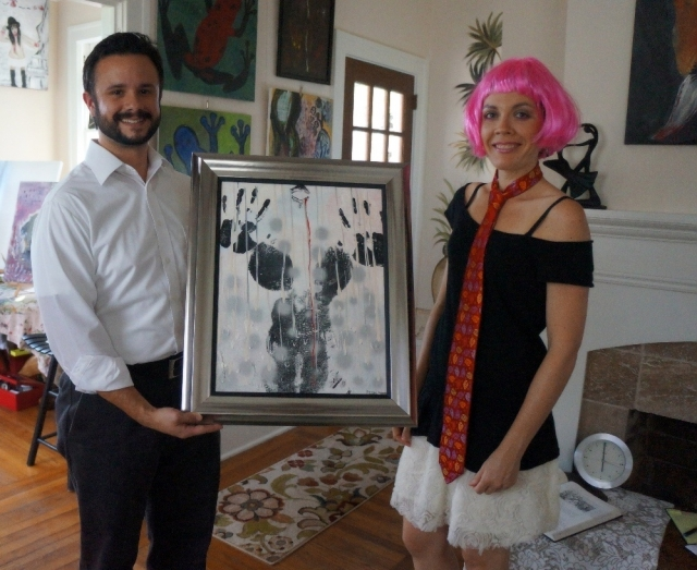 Artist Rachael Harbert stands next to a client holding a painting that he has purchased