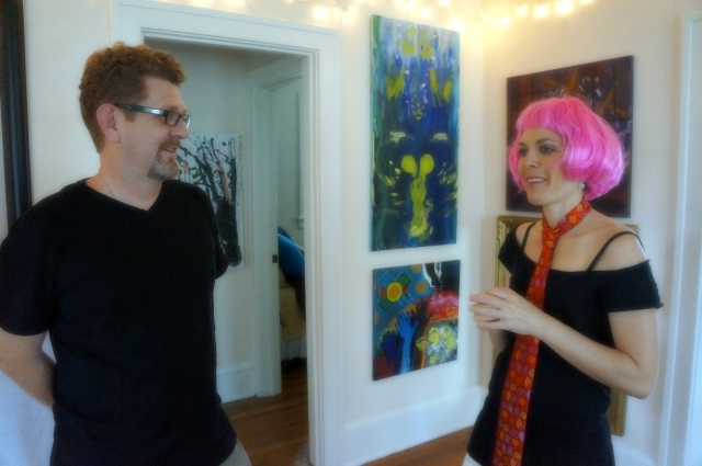 Artist Rachael Harbert chats with the author Mark David Major during an art show