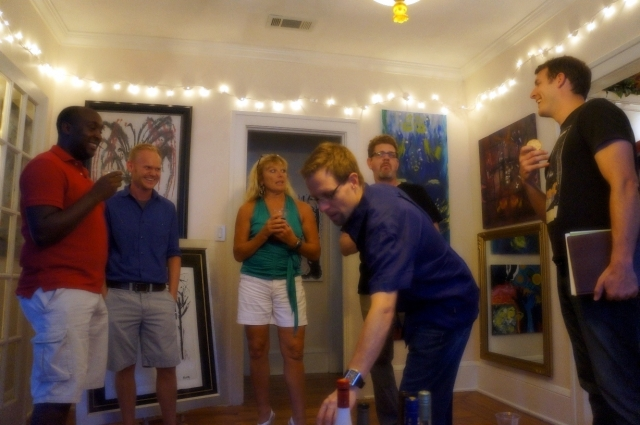 People stand around laughing and drinking wine at Rachael Harbert's in-home art show