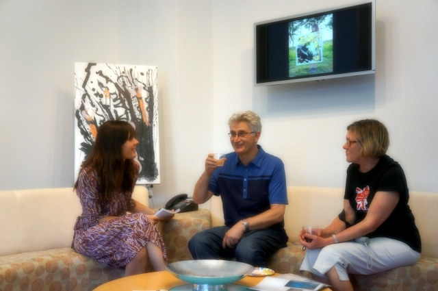 Artist Rachael Harbert talks with two people at her art show hosted by the Perdue company