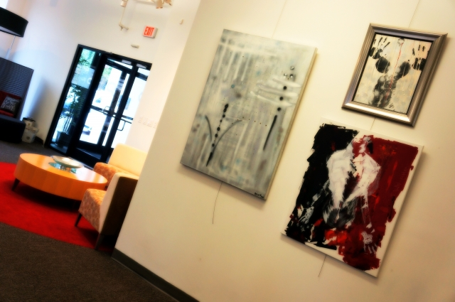 A display of 3 of Rachael Harbert's paintings at an art show hosted by the Perdue company
