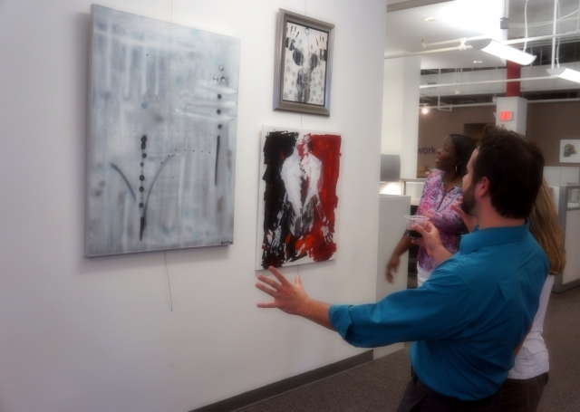 A client of artist Rachael Harbert becomes excited by her display of three paintings during her art show hosted by the Perdue company