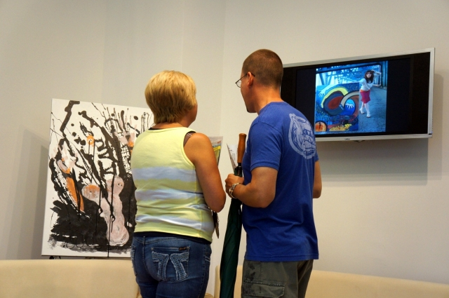 A man and a woman stand looking at one of Rachael Harbert's paintings during the art show hosted by the Perdue company