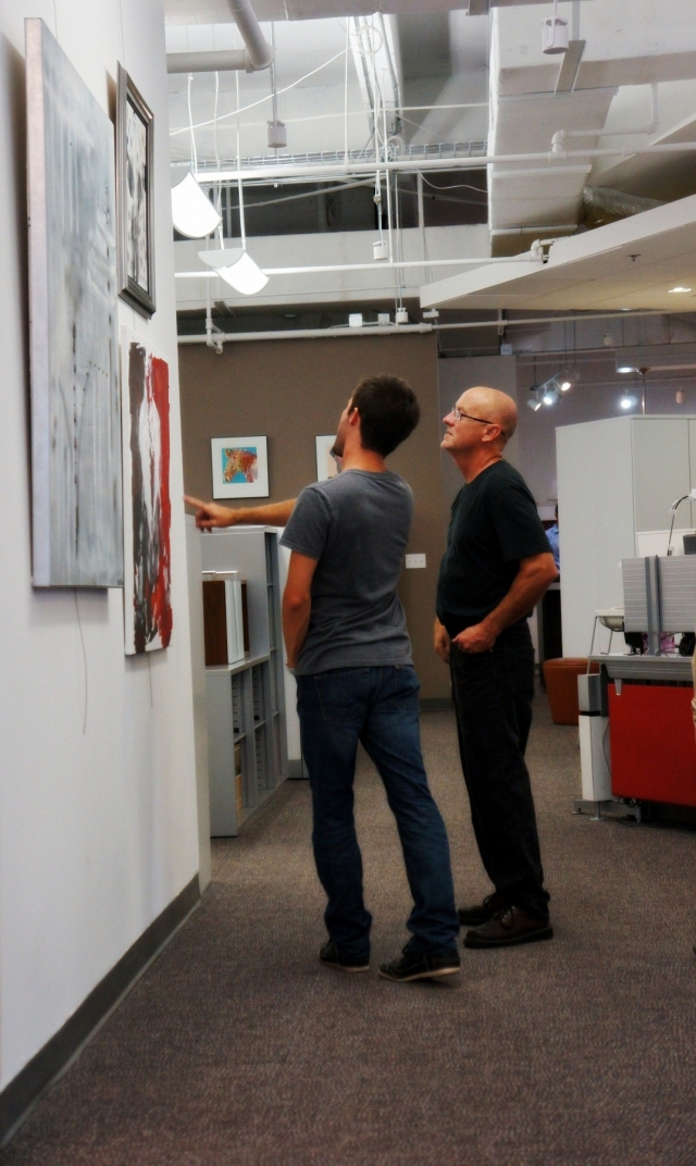 Two men discuss Rachael Harbert's paintings during her art show hosted by the Perdue company