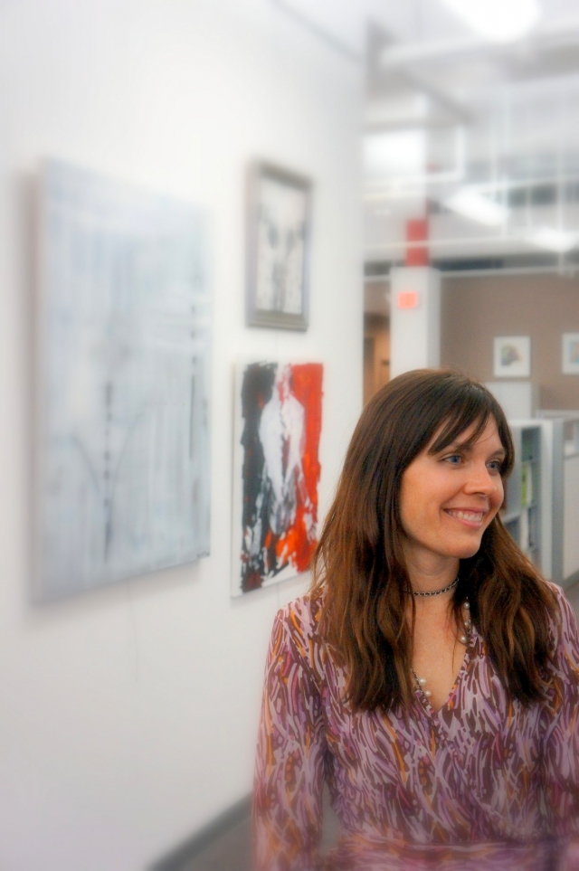 Candid picture of artist Rachael Harbert smiling during her art show hosted by the Perdue company