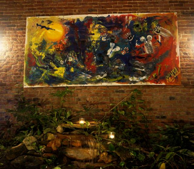 A nighttime photo of a huge abstract painting by Rachael Harbert hanging on a brick wall