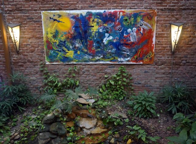 A daytime photo of a huge abstract painting by Rachael Harbert hanging on a brick wall