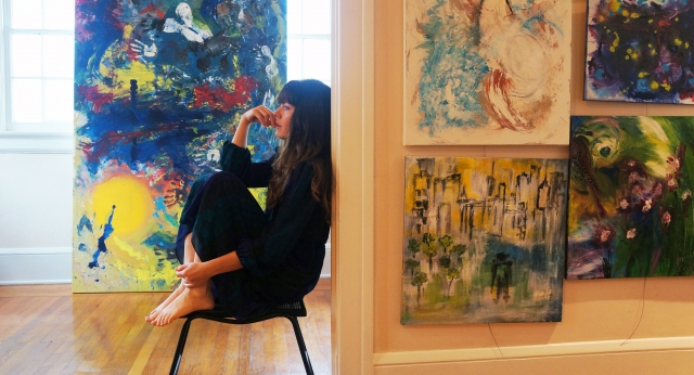 Artist Rachael Harbert sits in her home art studio with her paintings around her
