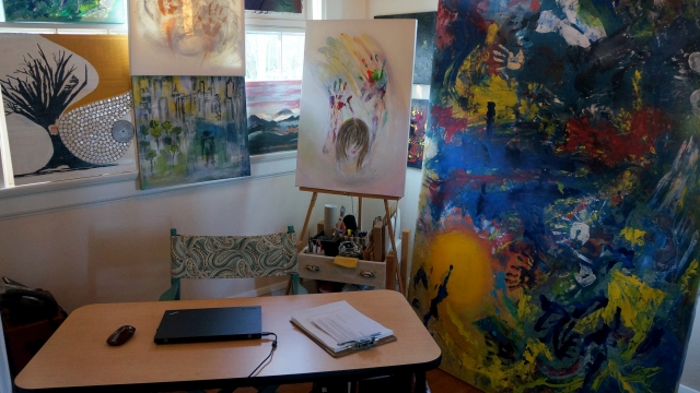 A view of Rachael's home art studio with various paintings