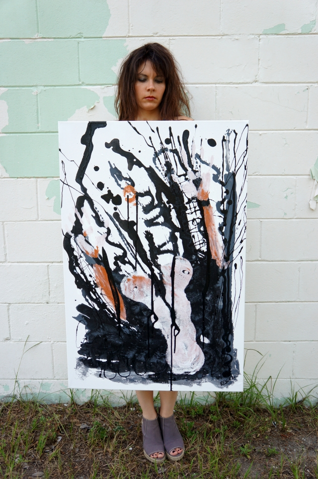 "Artist Rachael Harbert holding abstract expressionism painting ""Fireproof"" in front of a wall with peeling paint"