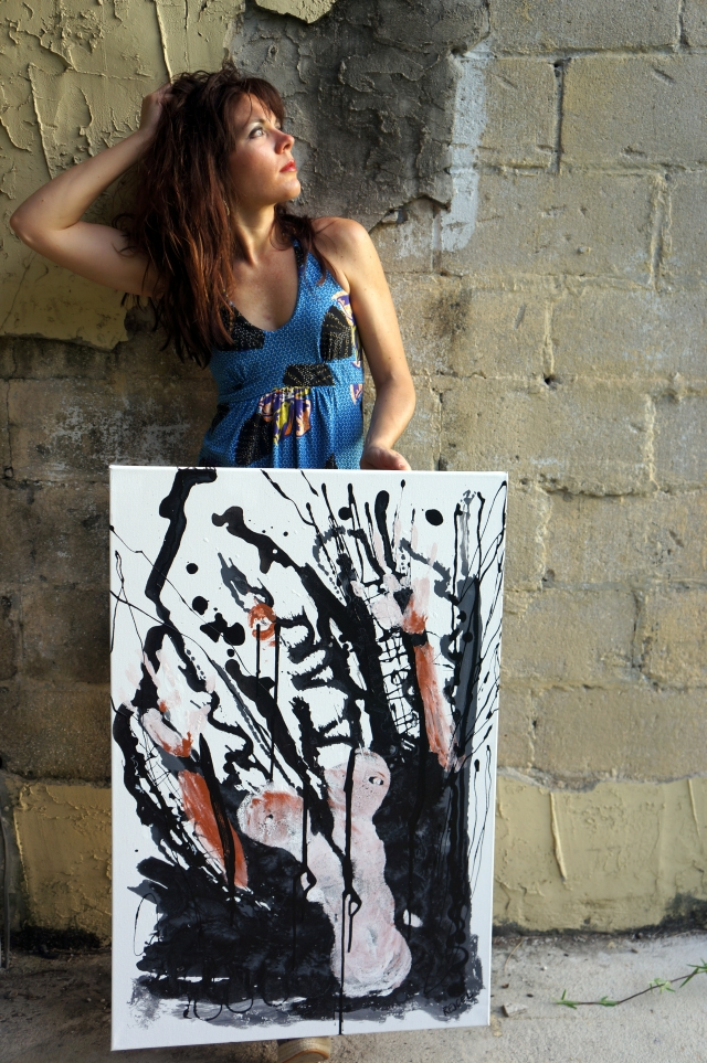 "Artist Rachael Harbert propping up abstract expressionism painting ""Fireproof"" in front of a rustic block wall"