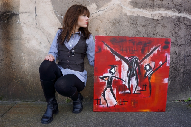 "Artist Rachael Harbert crouched and leaning against multi gray wall with painting ""Fight Test"" next to her"