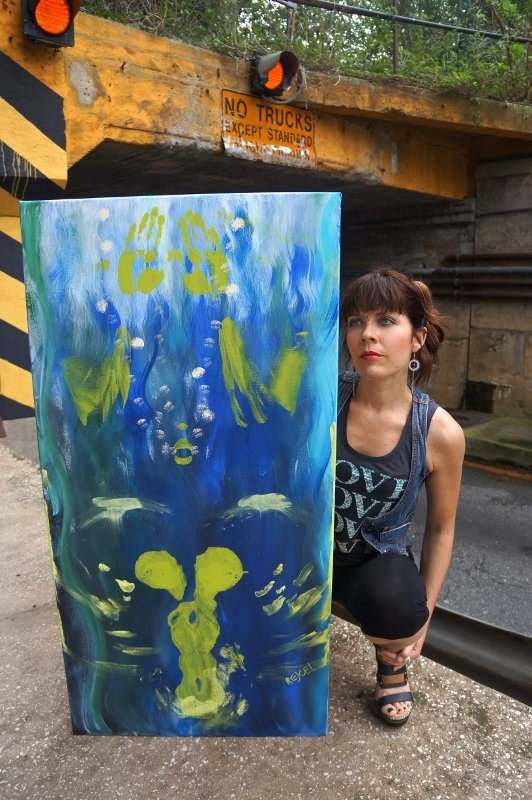 "Artist Rachael Harbert in front of train signals with abstract expressionistic painting entitled ""22.22 Degrees Celsius"""
